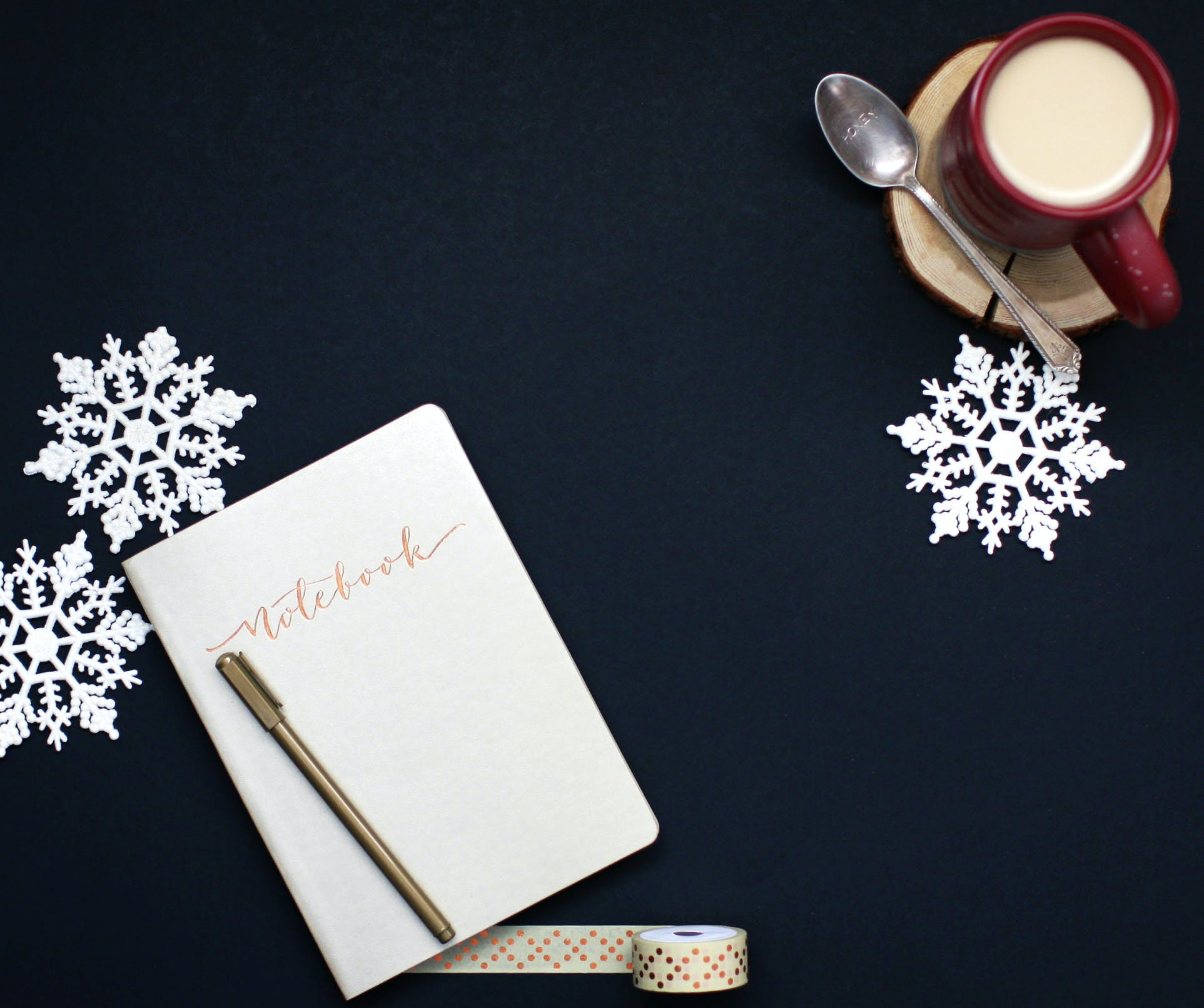 Brown Pen on White Notebook Near Red Coffee Mug and Silver Spoon on Top of Blue Surface