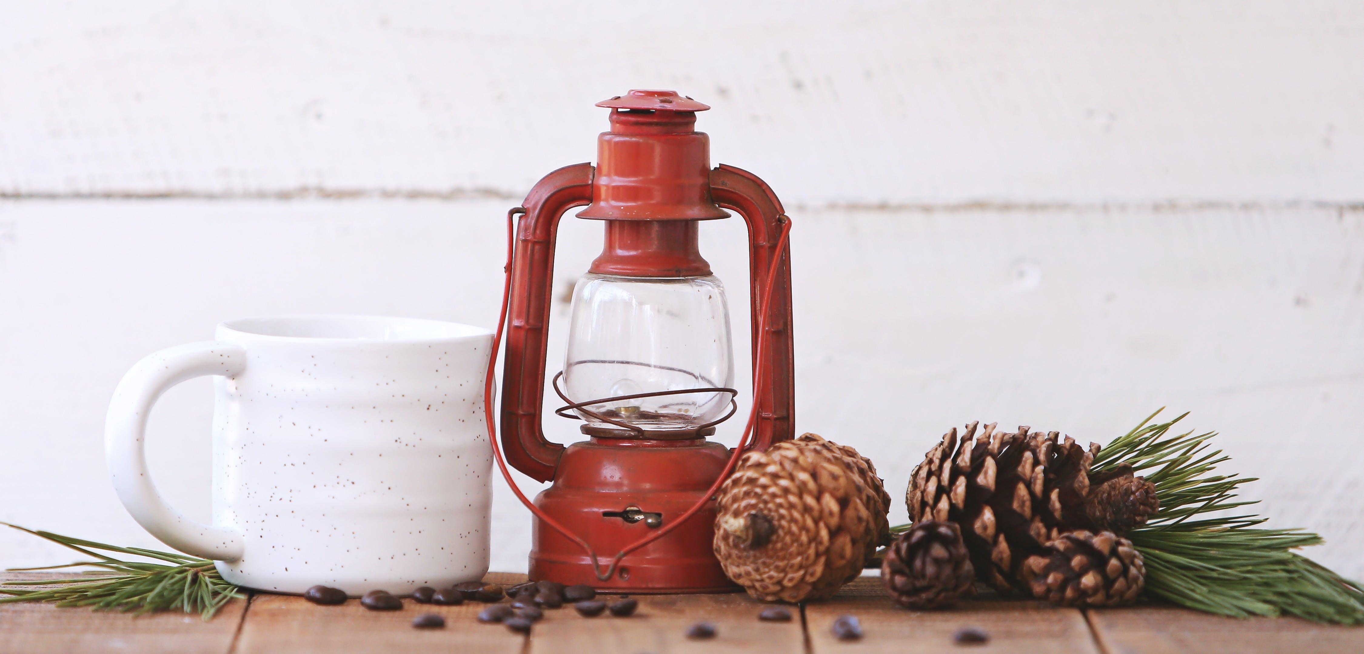 Red Kerosene Lantern Beside White Ceramic Mug on Brown Wooden Table