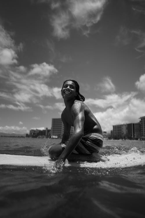 Black and white full body of happy young African American guy in swimsuit surfing on board in sea in day near city