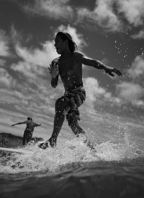 Black and white anonymous friends in swimsuits surfing together on surfboards in sea in day