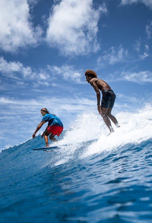 Multiethnic faceless friends surfing on boards in sea