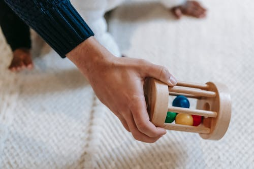 From above of crop anonymous male parent carrying colorful wooden rattle with small balls while spending time with little babyb