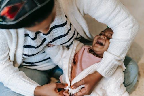 Une Mère Change Les Vêtements De Son Bébé