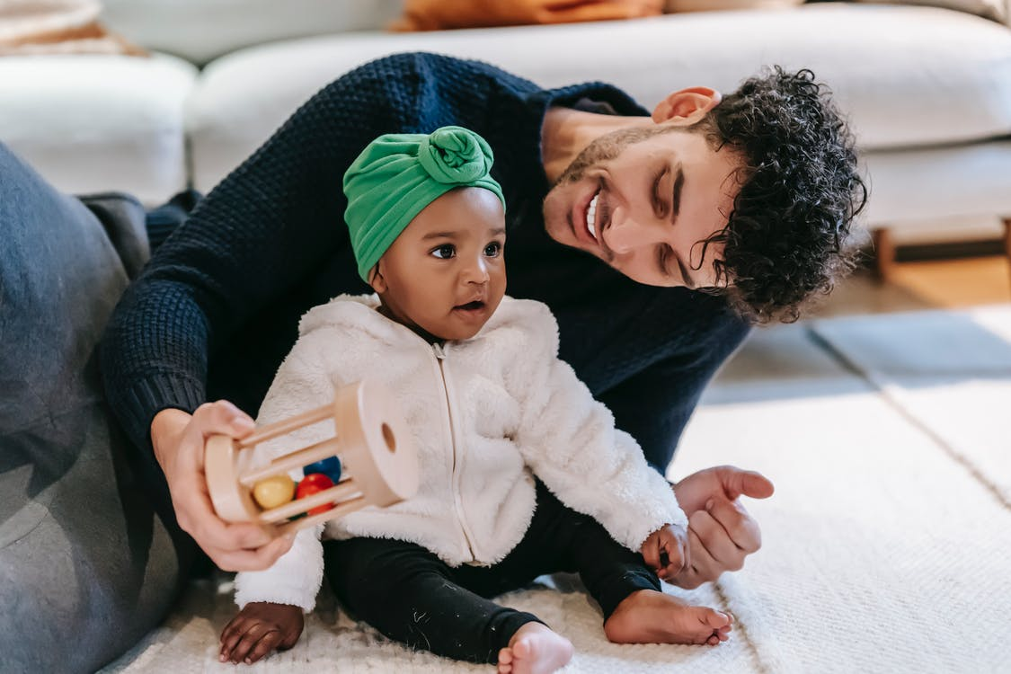 Smiling father playing with Indian baby girl at home