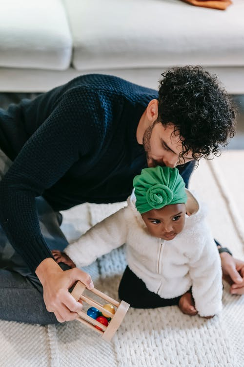 Multiracial father and baby playing together on floor