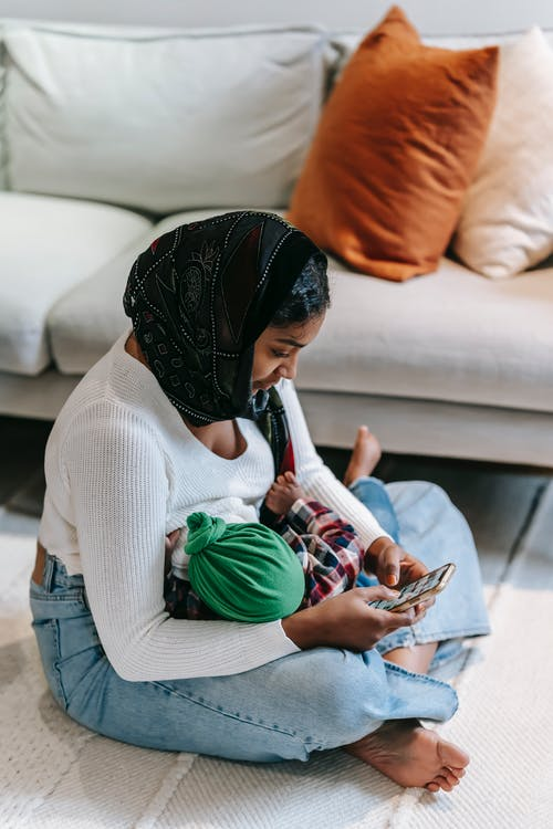 Side view of young Indian female in casual clothes and headscarf embracing newborn baby and messaging on mobile phone while sitting on floor in living room