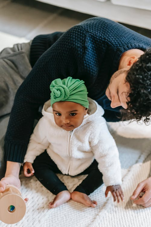 High angle of adorable little Indian child in turban sitting on floor while playing with crop young ethnic father at home