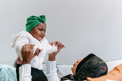 Black mother comforting capricious baby on couch