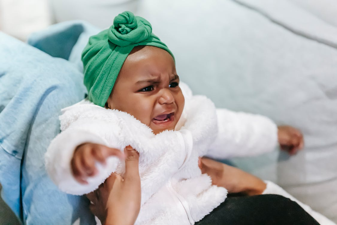 Crying black baby in turban in mother hands