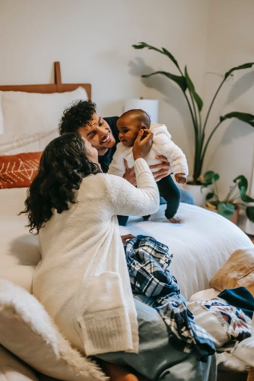 Happy diverse parents caressing adorable baby while sitting on bed