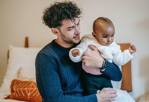 Caring ethnic bearded man caressing African American infant baby while sitting on bed in bedroom on blurred background at home