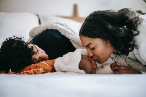 Young ethnic mother kissing baby sleeping near dad on bed