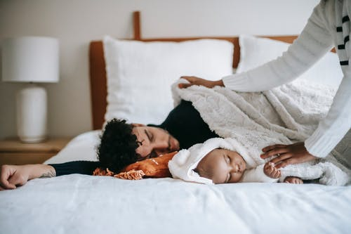Crop faceless black woman in casual clothes spreading blanket on diverse husband and baby sleeping together on soft bed in morning