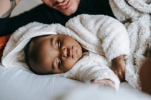 Unrecognizable ethnic father lying on bed with African American newborn baby in white pajama sleeping in bedroom during bed time at home