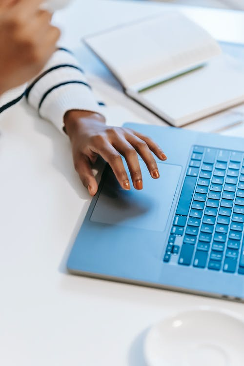 High angle of crop anonymous ethnic woman working remotely at white table on laptop near notebook with pen while drinking coffee in light workplace