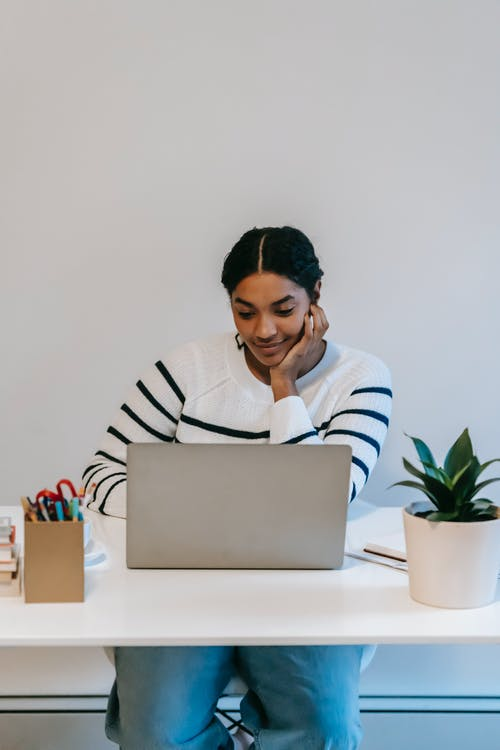 Concentrated young Indian female freelancer in casual outfit using netbook at table near potted green plant and holder for office supplies in bright workspace