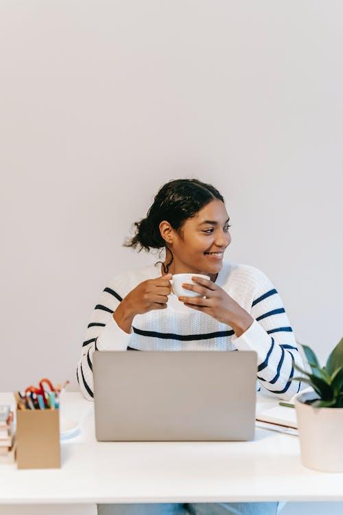Indian female freelancer using laptop with coffee mug in workspace