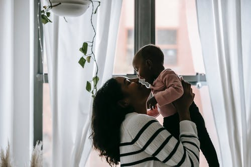 Side view of smiling ethnic mother holding baby in arms while wearing casual outfits in apartment near window with curtains under potted plant with green leaves in daylight