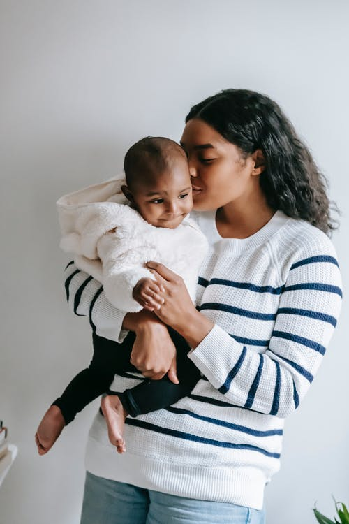 Ethnic mother kissing baby while holding in arms at apartment
