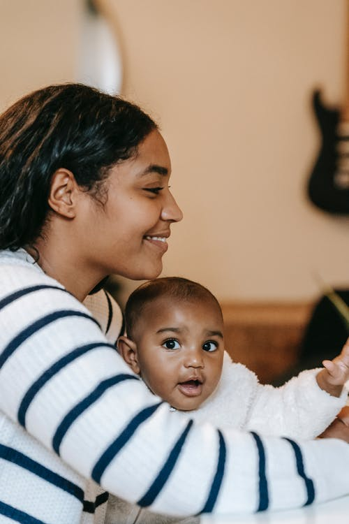 Positive ethnic lady with toddler in room at table