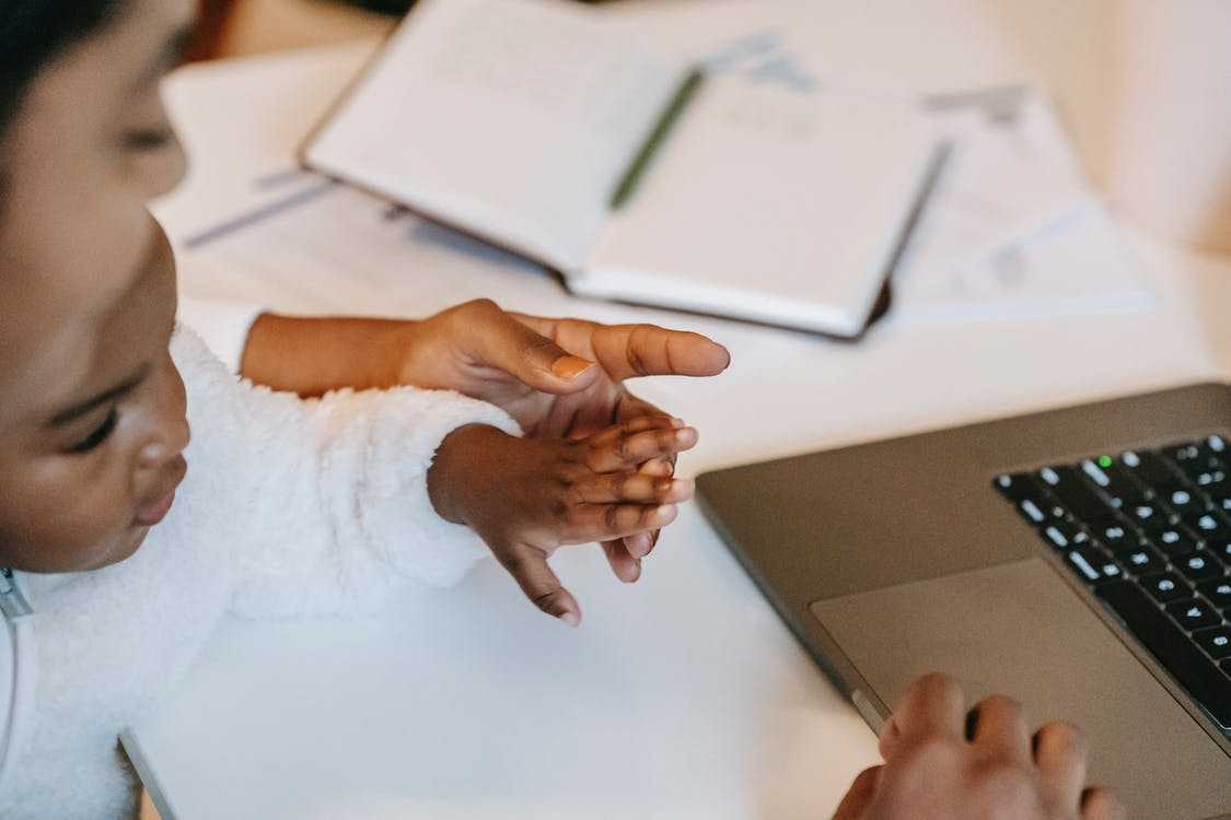 High angle of crop faceless ethnic toddler touching female hand in casual clothes and using laptop at table near opened notepad with pen in light room