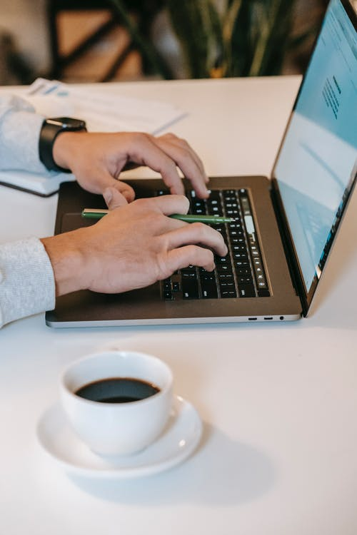 Student sitting at table with cup of coffee and browsing laptop
