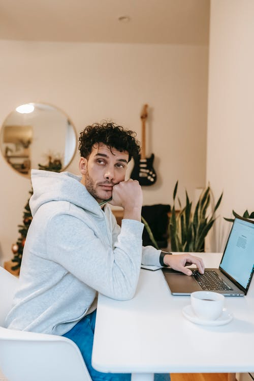 Side view of thoughtful freelancer in casual clothes sitting at table with cup of coffee and laptop while working on project at home in daytime
