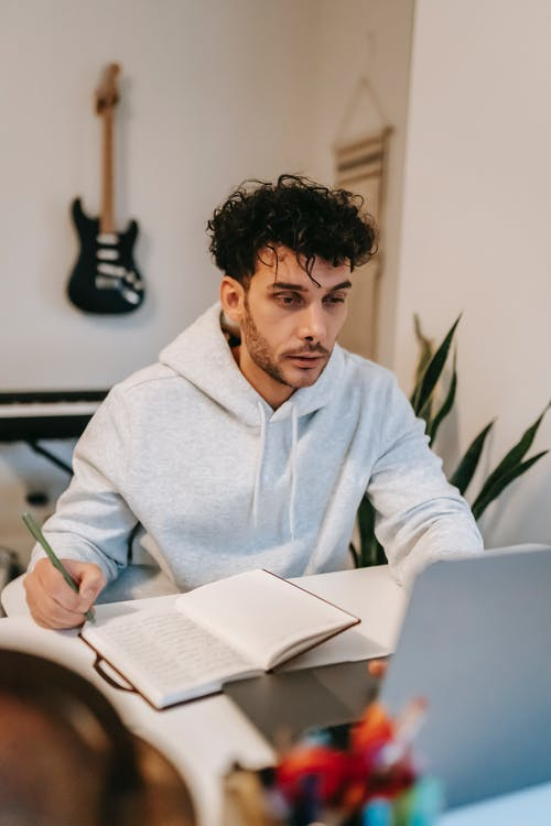 Young bearded male artist writing lyrics in agenda while surfing internet on portable computer in house