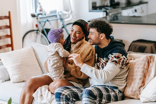 Happy diverse family talking to little girl on sofa indoors
