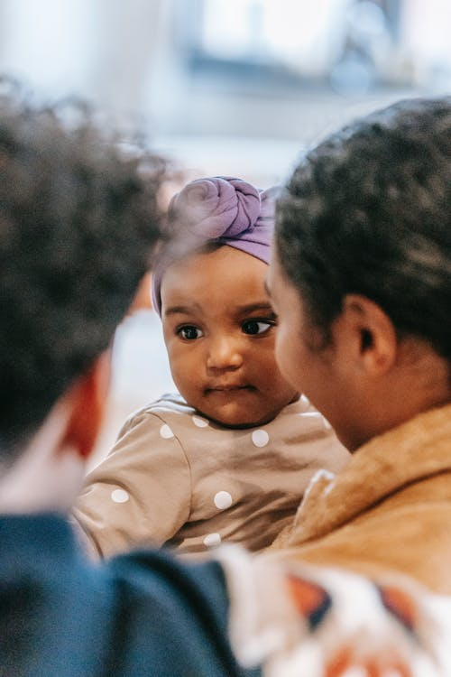 Crop unrecognizable multiethnic mom and dad interacting with adorable little girl while spending time together