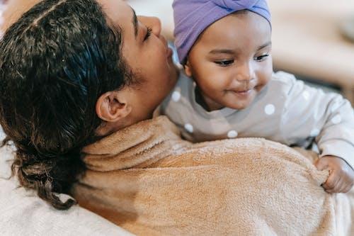 Crop black mother talking to smiling little daughter