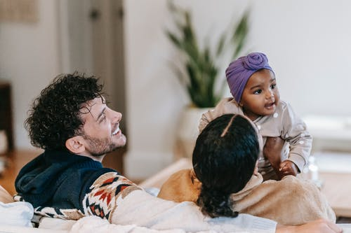 Unrecognizable ethnic mom interacting with cute toddler child near content bearded father in house room
