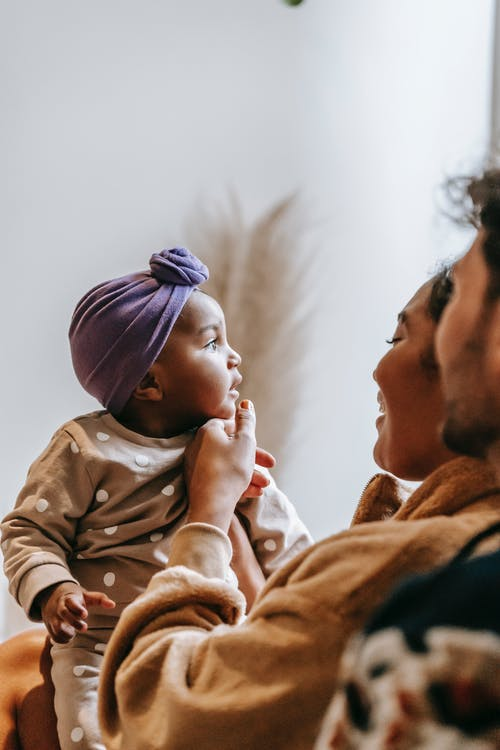 Crop anonymous bearded father near smiling black mom and contemplative little child in house room