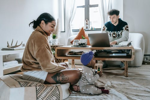 Full body of cheerful African American mother with little daughter sitting in living room near ethnic father browsing laptop during remote work