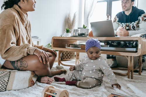 Full body of unrecognizable African American mother and little daughter sitting in living room with ethnic father browsing netbook at home