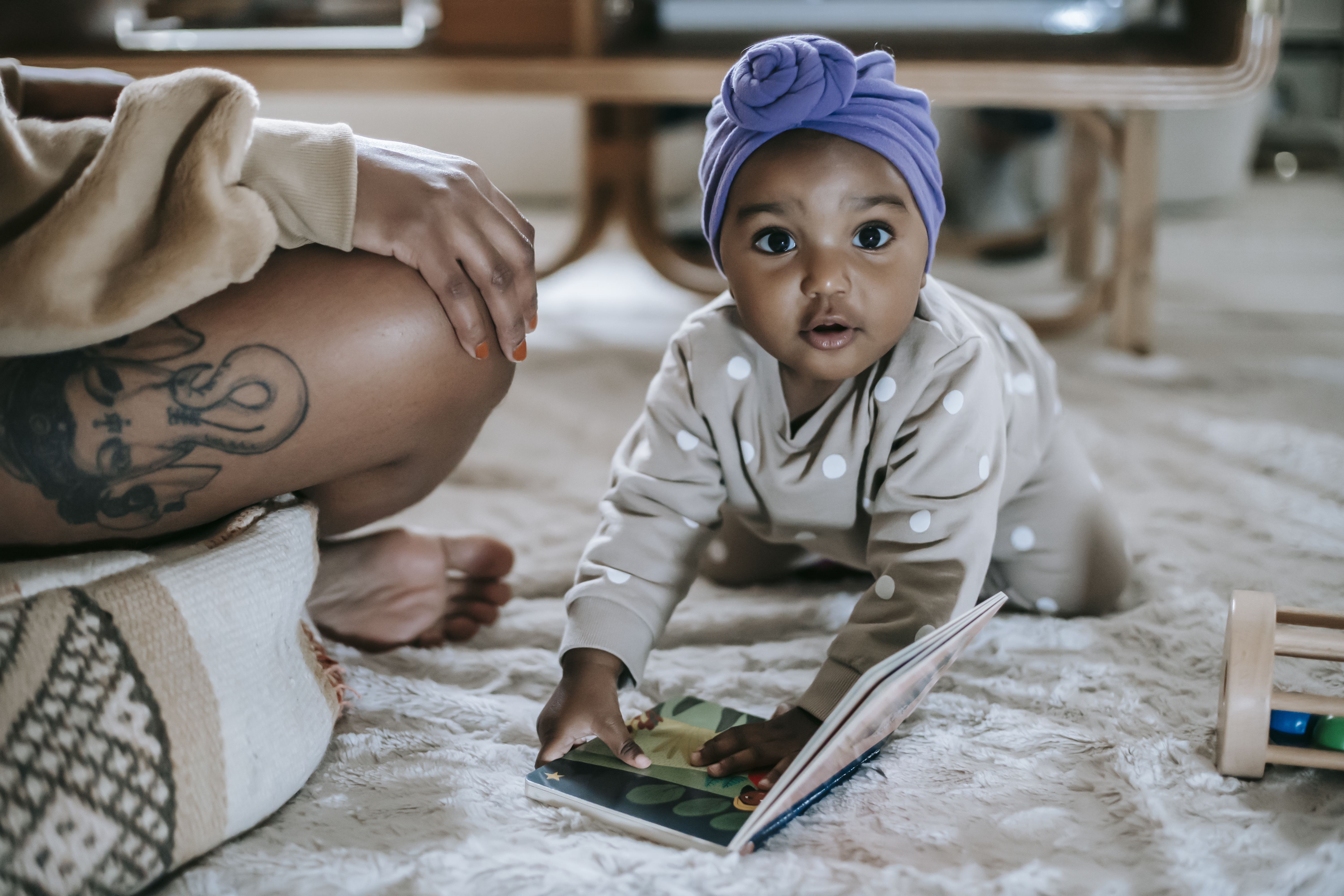 cute black baby with book in room with crop mother