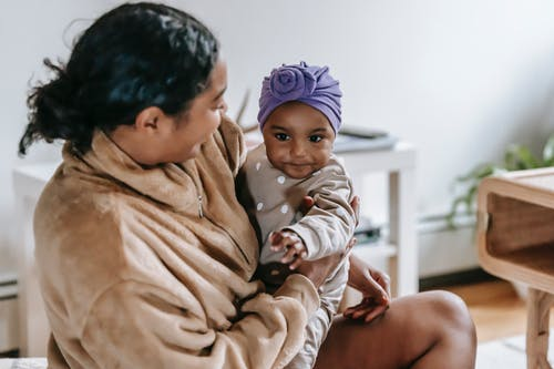 Positive African American mother looking at black little daughter on hands while spending time in living room on blurred background