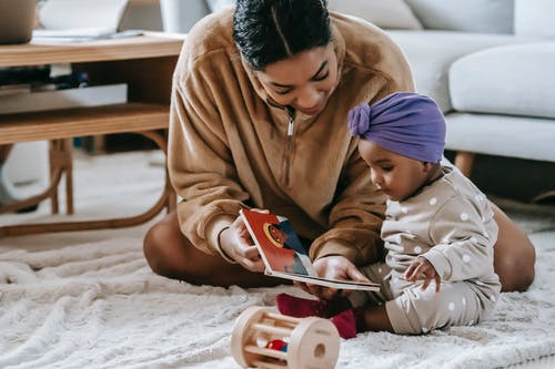 Black mother showing book to African American baby