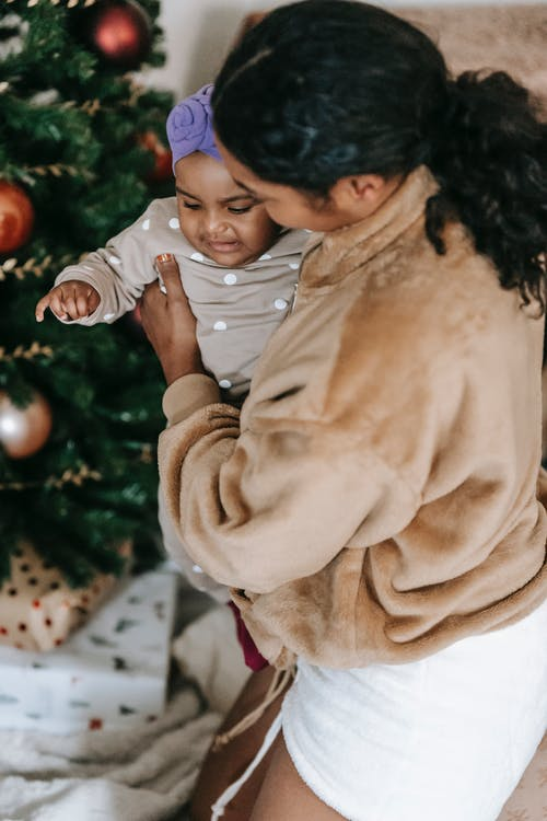 African American mother with little black baby on hands standing near decorated tree with baubles during Christmas holiday at home