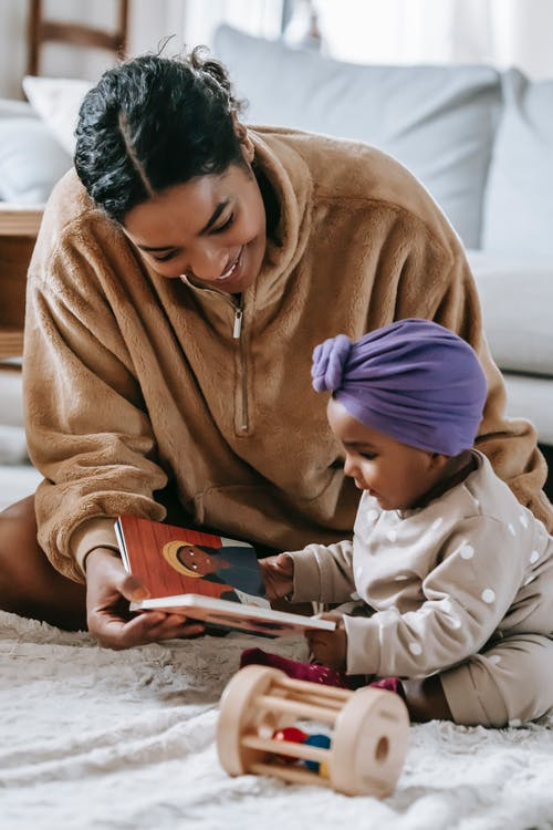Happy black mother demonstrating book to little black daughter