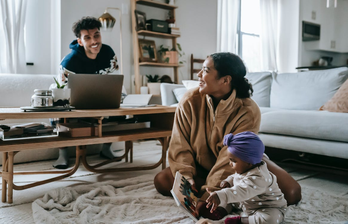 Positive African American mother and ethnic father near laptop looking at each other while spending time together at home with little black toddler