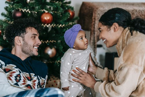 Happy diverse family with baby near Christmas tree