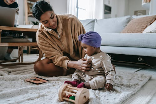 Black mother and little daughter on rug at home