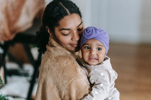Happy ethnic mother with little black daughter