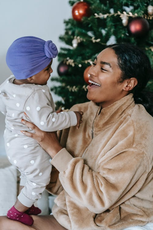 Side view of ethnic mother in casual clothes holding little daughter in hands in light room with Christmas tree