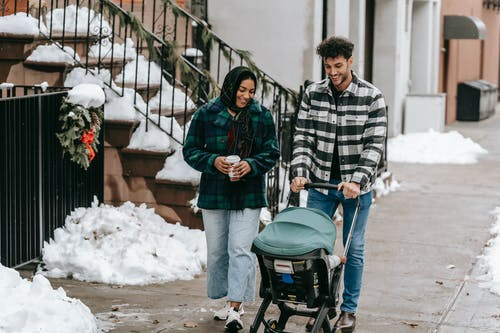 Positive ethnic couple having stroll with baby in stroller