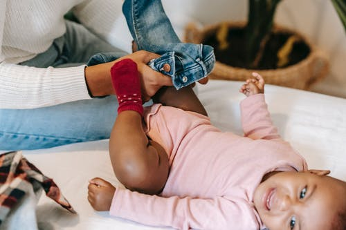 High angle of crop African American mother putting jeans on baby daughter crying on changing table