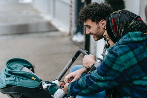 Ethnic couple smiling at baby lying in stroller