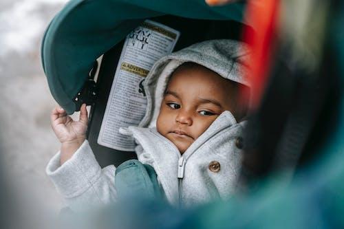 Little ethic baby in hood in stroller