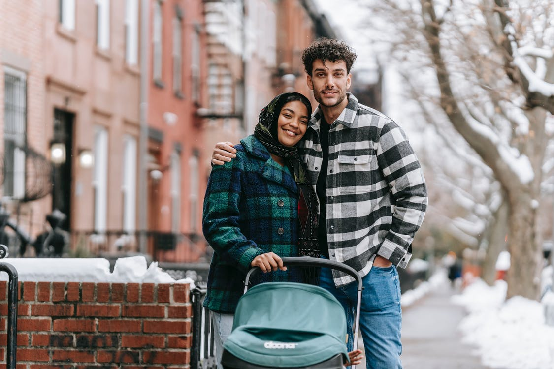 Loving ethnic parents hugging gently on sidewalk